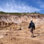 Colour photograph of a man walking across white rocks in the quarry