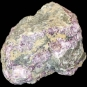 Colour image of gray rock mottled with with green, pink and yellow rock
