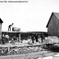 Black and white photograph of rock mine, buildings, sheds, rocks and man on roof of shed