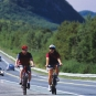 Colour photograph of two cyclists, highway and mountain in background