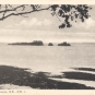 Black and white postcard of beach, water and rocky formations in the distance