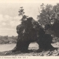 Black and white postcard of rocky beach with curved rock formation with hole in the centre