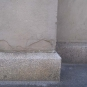 Colour photograph of slab of gray rock at base of building column