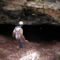 Colour photograph of a person walking into rock cave