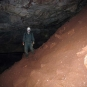 Colour photograph of person in green coveralls and white hard hat standing inside rock cave