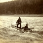 Black and white photograph of two men in a canoe, one standing, shooting rapids