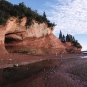 Colour photograph of a red rock cliff on the ocean