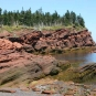 Colour photograph of a red sandstone rock on the ocean with a beach and trees on top of the cliff