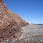 Colour photograph of a beach with red clay cliffs and the ocean