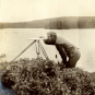 Black and white photograph of man standing in front of a lake with surveying equipment