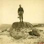 Black and white photograph of man standing on a large boulder